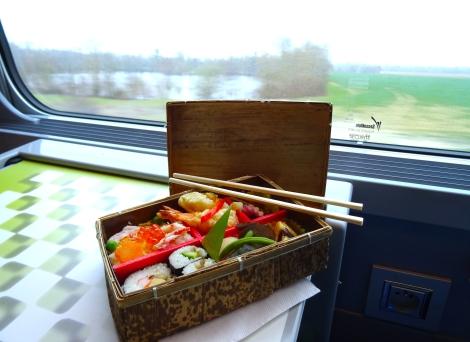 Ekiben, un bentô acheté dans une gare et mangé dans le train, acheté au Bento de la Gare à Paris, Gare de Lyon. Ici, le contenu du menu Omotenashi, avec paysage derrière.